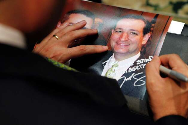 U.S. Senate candidate Ted Cruz signs a picture of himself after speaking to the Texas delegation at the Saddlebrook Resort in Wesley Chapel, Florida on Monday, August 27, 2012. (Lara Solt/Dallas Morning News/MCT) Photo: Lara Solt, McClatchy-Tribune News Service / Dallas Morning News
