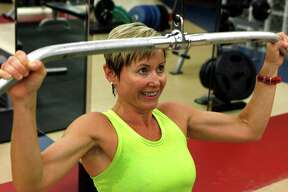 Gina Garcia, the assistant fitness director at SMU, works with a pull down cable during a workout out at SMU's Dedman Center in University Park, Texas, Wednesday, July 25, 2012. (Ron Heflin/Dallas Morning News/MCT)