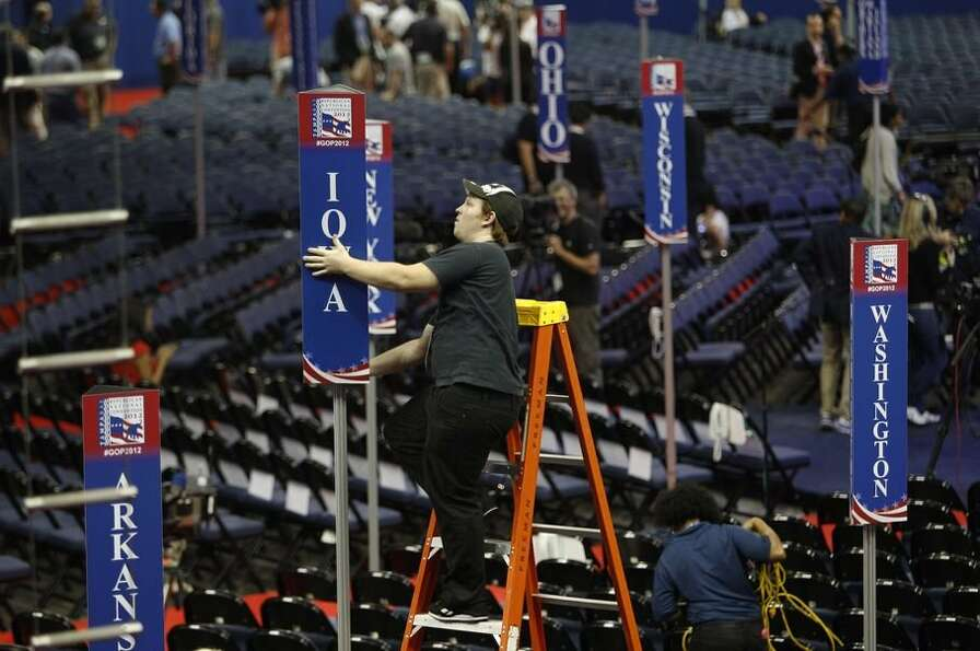 Scott Kiss of Tampa installs an Iowa delegate sign on the floor of the Republican National Conventio