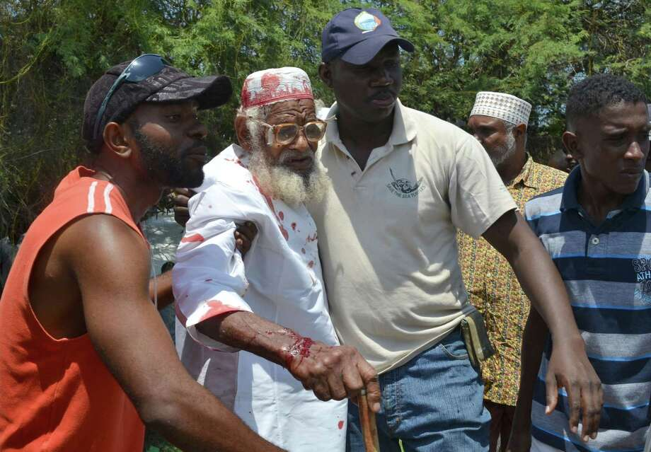 A relative of Aboud Rogo is assisted at the scene where the a Muslim cleric facing terror-related charges was shot to death Monday in Mombasa, Kenya. Photo: Stringer / AP