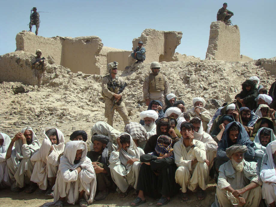 U.S. soldiers stand guard as Afghan men listen to speeches Saturday in Helmand province, Afghanistan. Seventeen bodies were discovered there hours later. Photo: Abdul Khaleq / AP