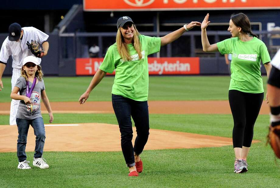 Christie Rampone, center, member of the gold medal-winning United States women's soccer team at the 2012 London Summer Olympics, high-fives figure skater Sarah Hughes after they threw out the ceremonial first pitch before a baseball game between the New York Yankees and the Toronto Blue Jays, Monday, Aug. 27, 2012, at Yankee Stadium in New York. At left, Rampone's daughter, Rylie, 6, wears her mother's gold medal. (AP Photo/Kathy Kmonicek) Photo: Kathy Kmonicek, Associated Press / FR170189 AP