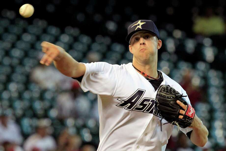 Houston Astros starting pitcher Jordan Lyles attempts a pick off at first base during the first inning of a baseball game at Minute Maid Park Sunday, Aug. 12, 2012, in Houston. (Cody Duty / Houston Chronicle) Photo: Cody Duty / © 2011 Houston Chronicle