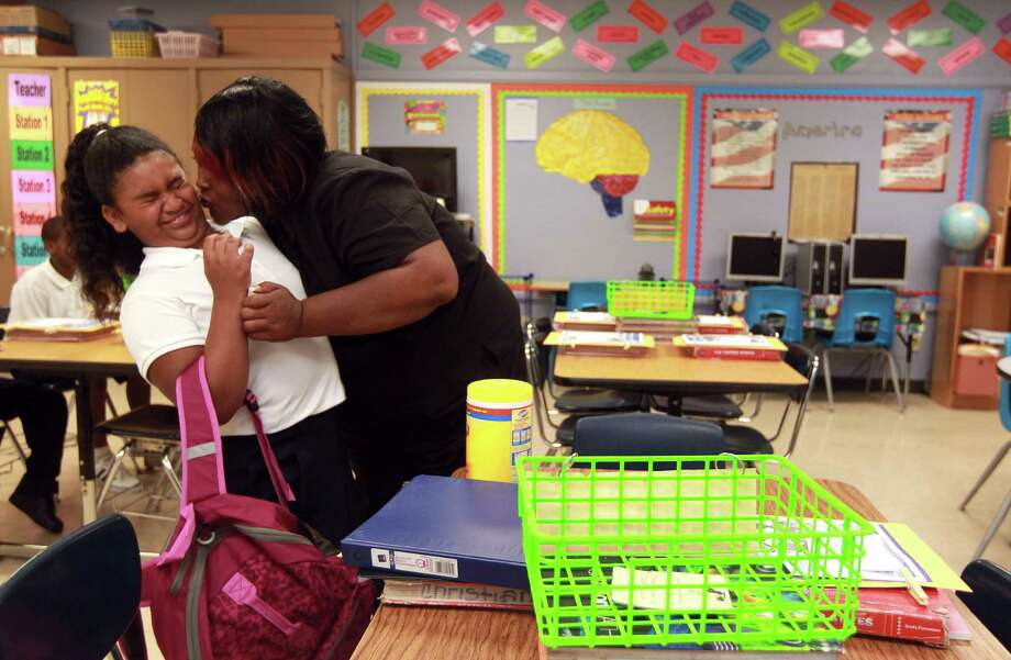 London Britton, 10, pulls away as her mother, Rosina Britton, gives her a goodbye kiss in her new classroom on her first day at a new school, Whidby Elementary. Photo: Johnny Hanson / © 2012  Houston Chronicle