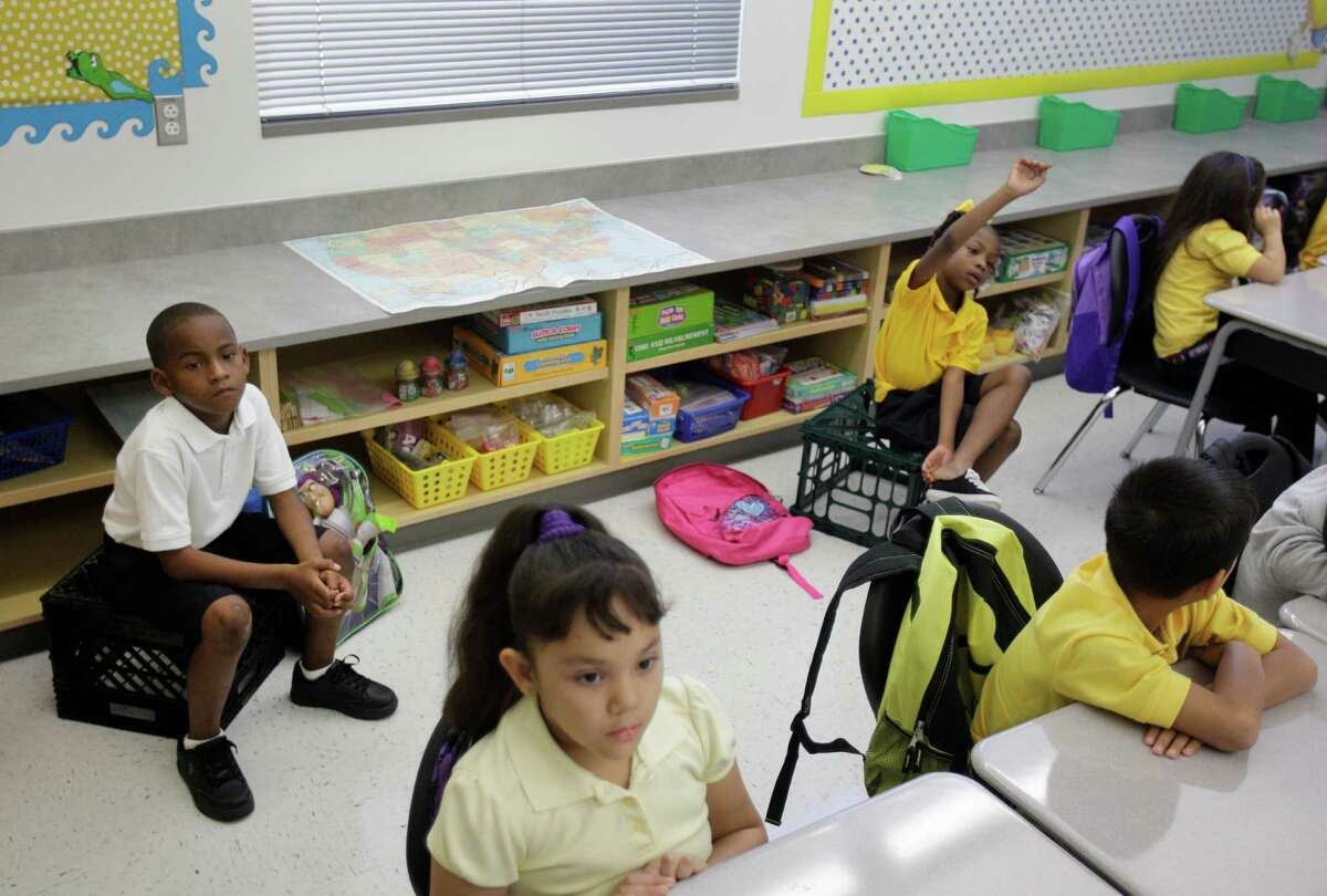 Terrance Thomas, 6, left, and another first-grade classmate were without desks in the classroom of Kimberly Marks on the first day of school at the new Billy Reagan K-8 Education Center in Houston.