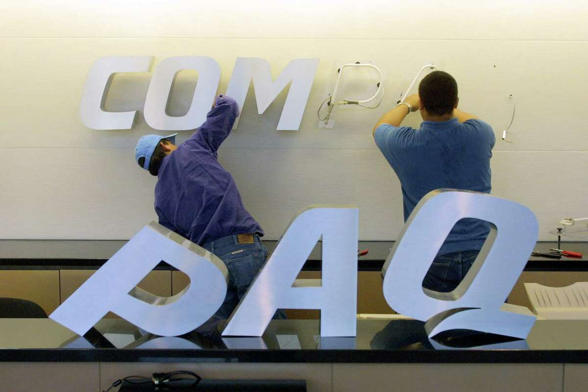 Electricians change the Compaq sign at the company's campus in Houston in May 2002. An analyst traces Hewlett-Packard's troubles to its acquisition of Compaq.