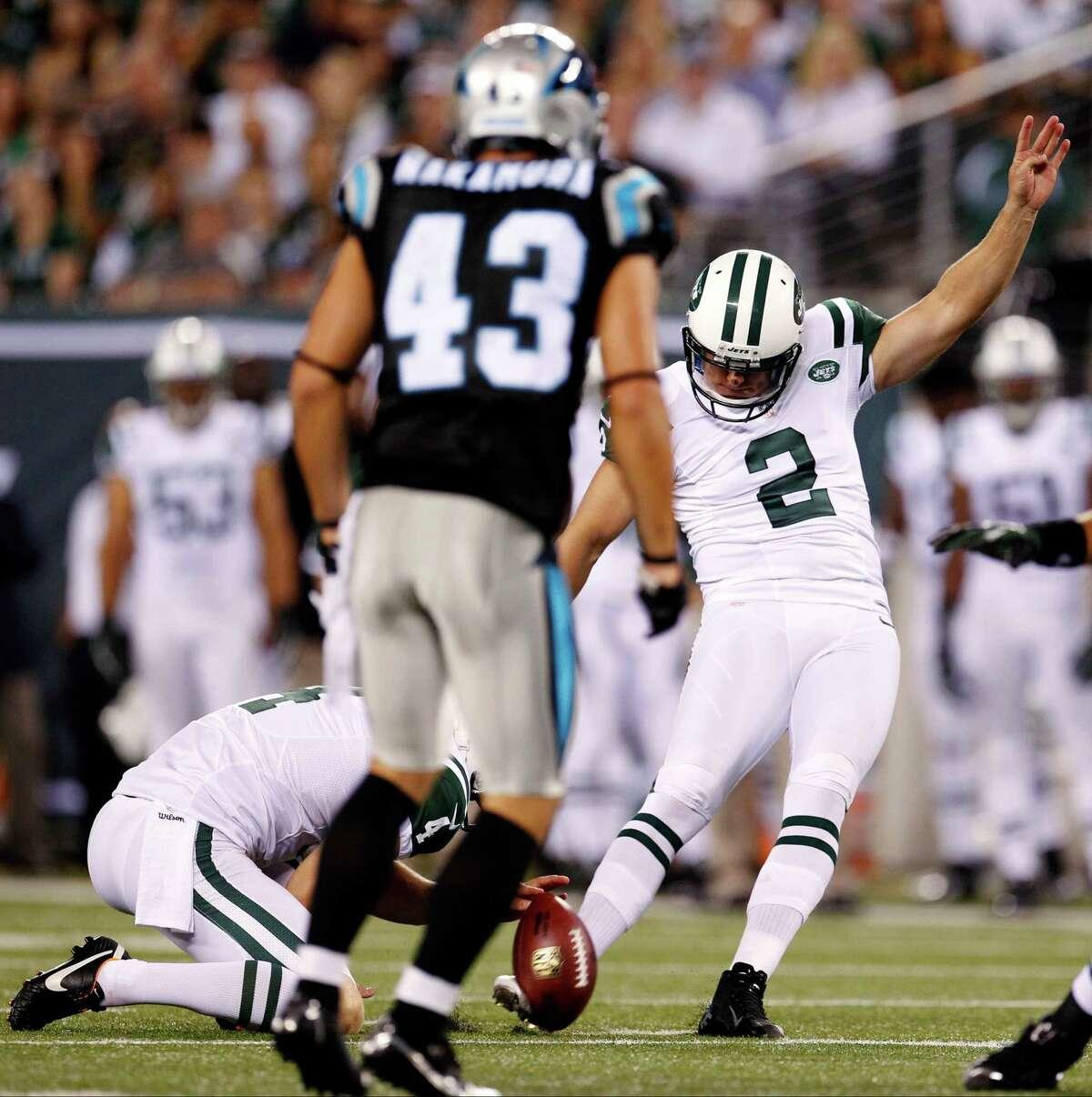 New York Jets kicker Nick Folk (2) kicks a field goal as Carolina Panthers' Haruki Nakamura (43) defends during the first half of a preseason NFL football game, Sunday, Aug. 26, 2012, in East Rutherford, N.J. (AP Photo/Julio Cortez)