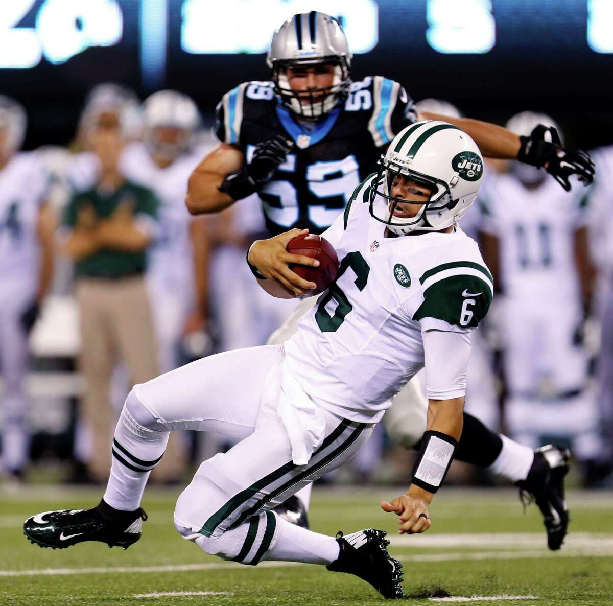 New York Jets quarterback Mark Sanchez (6) slides to avoid contact as Carolina Panthers linebacker Luke Kuechly (59) trails the play during the first half of a preseason NFL football game, Sunday, Aug. 26, 2012, in East Rutherford, N.J. (AP Photo/Julio Cortez)