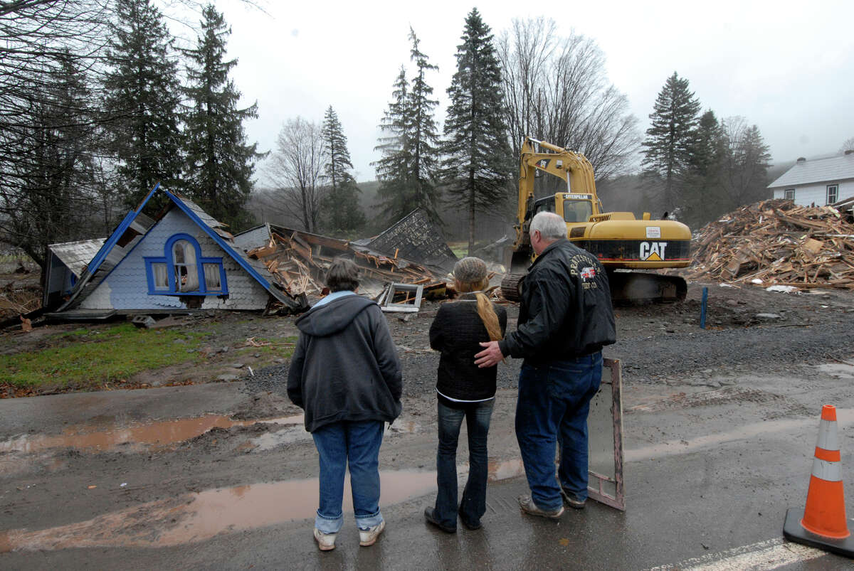 Prattsville, N.Y., November 23, 2011 -- Evelyn Rikard ,left, Ella Trec, center, and Dave Rikard,looks on as his home at 14602 Main street is demolished with an excavator for safty reasons, after flooding from Hurricane Irene. FEMA plays a vital role supporting State, Tribal and local governments as they respond to the impacts of Hurricane Irene. Hans Pennink/FEMA