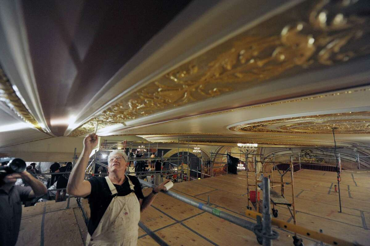 Terry Brackenbury, site foreman with Evergreene Architectural Arts brushes the composition leaf to remove the excess on the ceiling inside Proctors Theatre on Monday, Aug. 27, 2012 in Schenectady, NY. Theatre officials held a press event to unveil the restoration work that has been done to the ceiling. The project was funded in part by a $100,000 award Proctors received through state's Regional Council initiative. The composition leaf is made to imitate gold. (Paul Buckowski / Times Union)