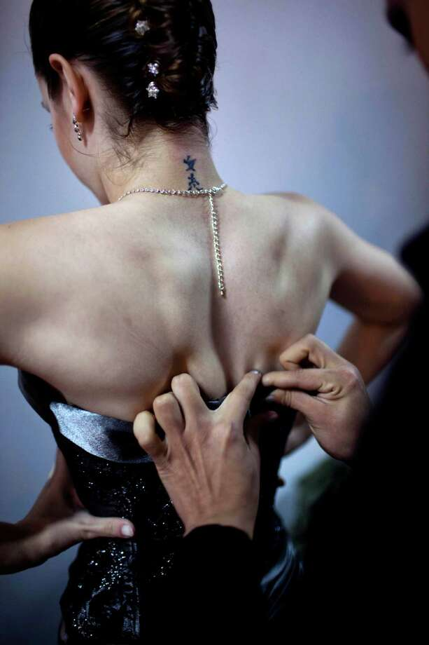 A dancer is helped to dress backstage before competing during the 2012 Tango Dance World Cup in Buenos Aires, Argentina, Monday, Aug. 20, 2012. The two-week long event offers more than 500 free dance lessons, concerts and recitals. Hundreds of professional dancers compete in the championship and teach many the eight basic steps of the dance in the city where it was born. Photo: Natacha Pisarenko, AP / AP