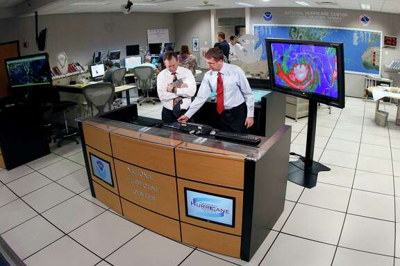 Dr. Rick Knabb, director of the National Hurricane Center, right, checks on the status of Tropical Storm Isaac as James Franklin, chief hurricane specialist, looks on at the National Hurricane Center in Miami, Tuesday, Aug. 28, 2012. Forecasters at the National Hurricane Center warned that Isaac, especially if it strikes at high tide, could cause storm surges of up to 12 feet (3.6 meters) along the coasts of southeast Louisiana and Mississippi and up to 6 feet (1.8 meters) as far away as the Florida Panhandle. (AP Photo/Alan Diaz)