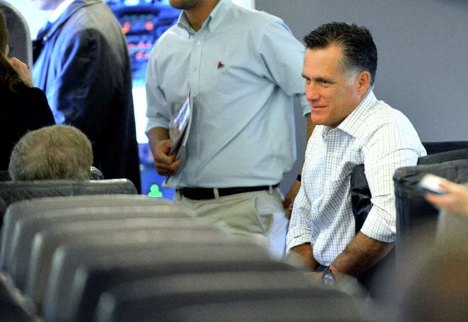 Mitt Romney speaks with a staffer en route to Tampa, Fla., site of the GOP national convention. This is no Etch A Sketch candidate: He's still pandering to right-wing core conservatives. Photo: Jewel Samad, AFP / Getty Images / AFP