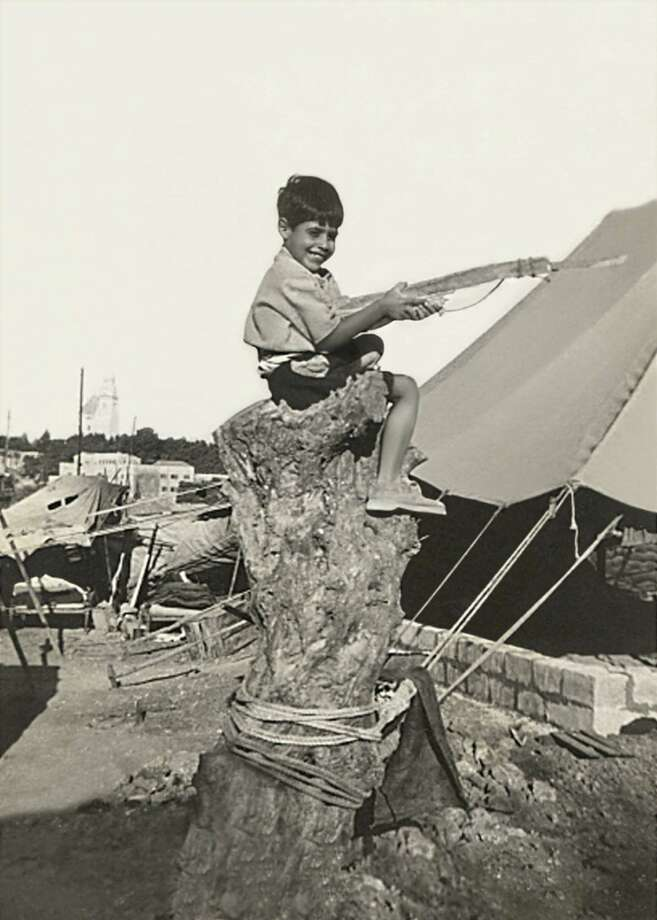 Jacob Nammar in 1947, age 6, sits on a tree stump in Jerusalem, Palestine at a British Mandate camp, defending Jerusalem with a toy gun. Jacob and all his family were forced out of their home and became refugees. Jacob immigrated to the United States of America in 1964 at the age of 23. Photo: Then & Now (Nammar)