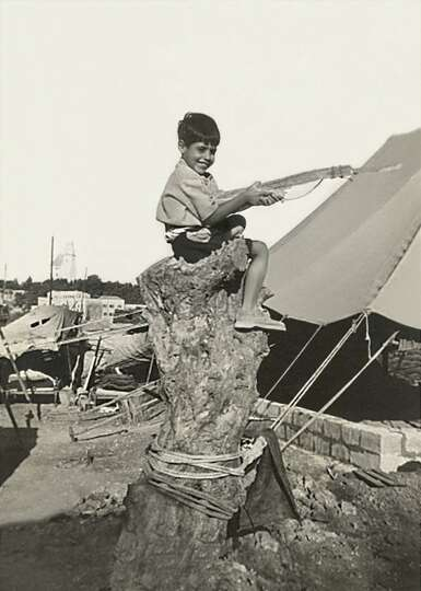 Jacob Nammar in 1947, age 6, sits on a tree stump in Jerusalem, Palestine at a British Mandate camp,