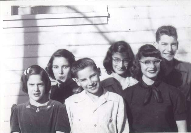 Nancy Bowman, nee Austenfeld, poses with her five younger siblings outside Robert s Market, their father s grocery store in Yakima, Wash., circa 1948.  From left to right, they are Mary Sue, Sally, Robert, Bonnie, Nancy, and John.  The photos was probably taken by their mother, Anne Kelly Austenfeld.