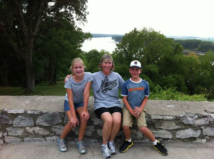 With the Missouri River Susan Oswald James sits with her grandchildren Lauren and Dylan Domel in a p