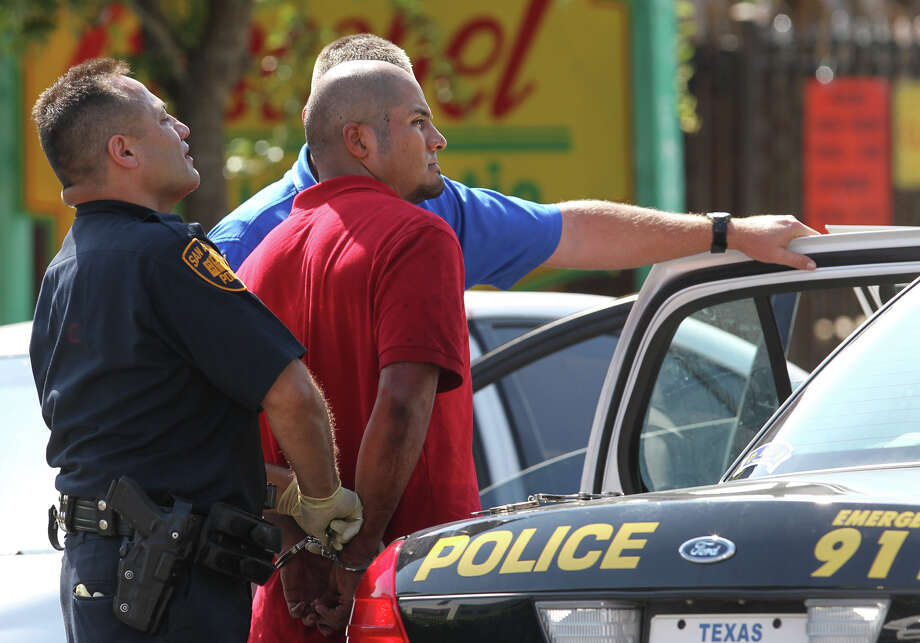 San Antonio police detain a suspect at the scene of a stabbing that took place Tuesday August 28, 2012 in front of Bonham Academy on S. St. Mary's street. Police said a woman was dropping her daughter off at the school when the man stabbed her. The woman is in critical condition. Photo: John Davenport, San Antonio Express-News / San Antonio Express-News