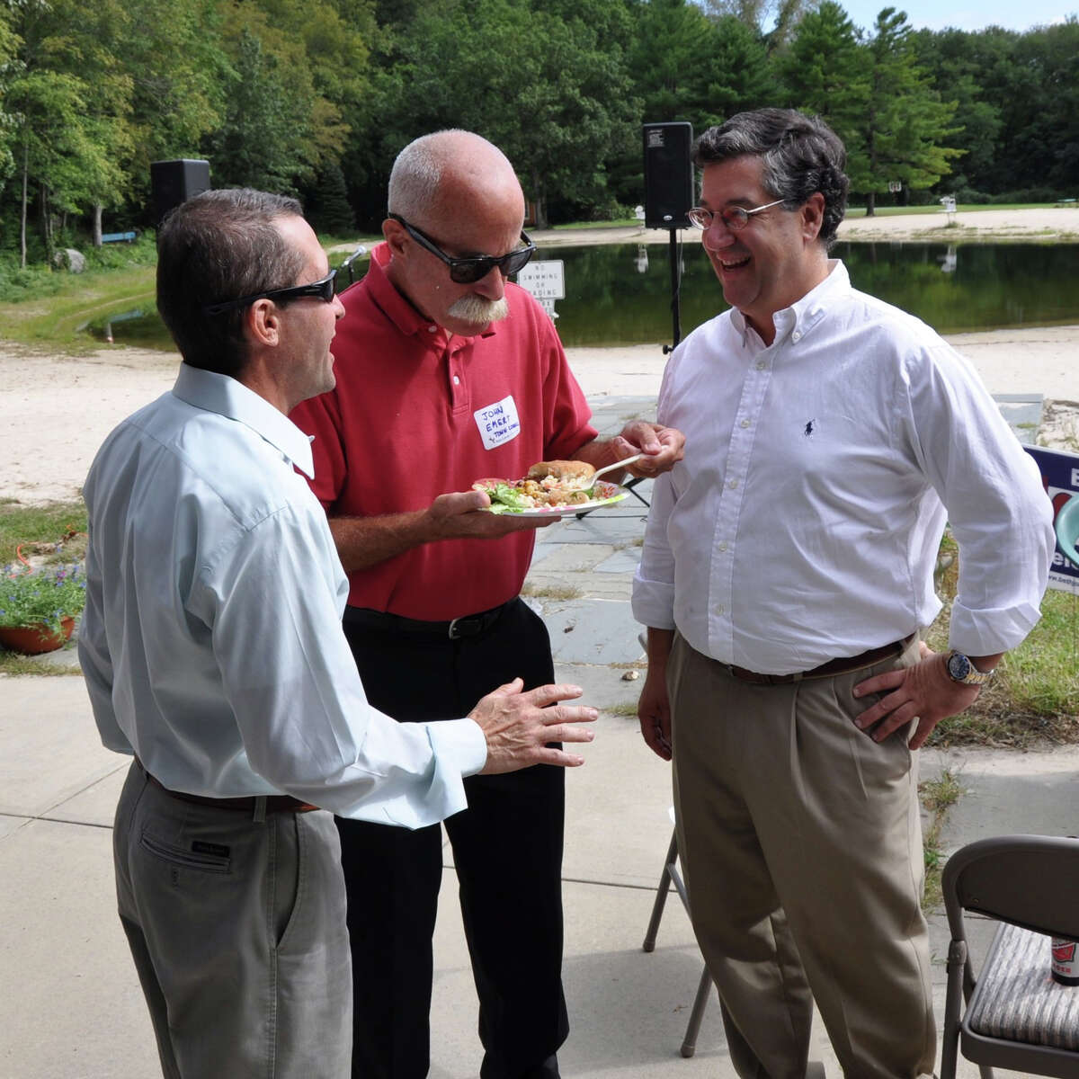 At the 2011 Democratic Town Committee barbecue, Town Council member John Emert, center, and First Selectman Rob Mallozzi, right, speak with a voter.