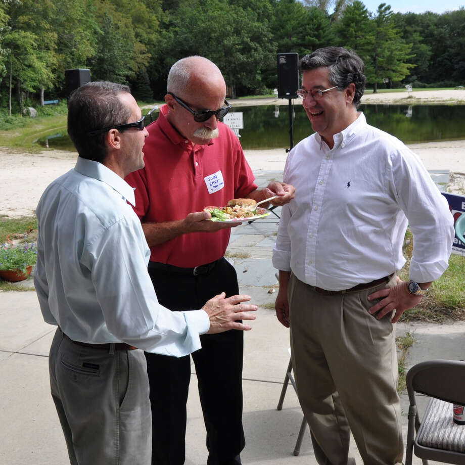 At the 2011 Democratic Town Committee barbecue, Town Council member John Emert, center, and First Selectman Rob Mallozzi, right, speak with a voter. Photo: Contributed