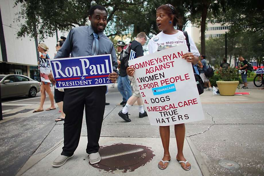 TAMPA, FL - AUGUST 28:  Darrell Young (L) a supporter of former Republican presidential candidate U.S. Rep. Ron Paul (R-TX) debates with Tonya Wieman a supporter of President Barack Obama as they stand together as they protest on the first full day of the Republican National Convention at the Tampa Bay Times Forum on August 28, 2012 in Tampa, Florida. The Republican party delegates were prepared to affirm Mitt Romney as the party's nominee as the convention began its first full session after the start was delayed due to Tropical Storm Isaac. Photo: Joe Raedle, Getty Images