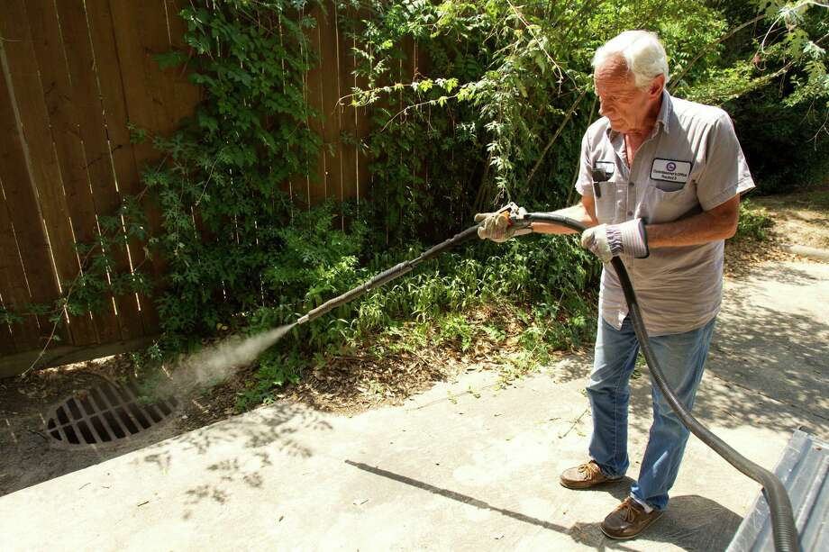 Paul Culbertson, of Montgomery County Precinct 3, sprays a storm drain to fight mosquitoes in June in The Woodlands. Recent testing in the area has shown an increase in West Nile virus. Photo: Brett Coomer / © 2012 Houston Chronicle