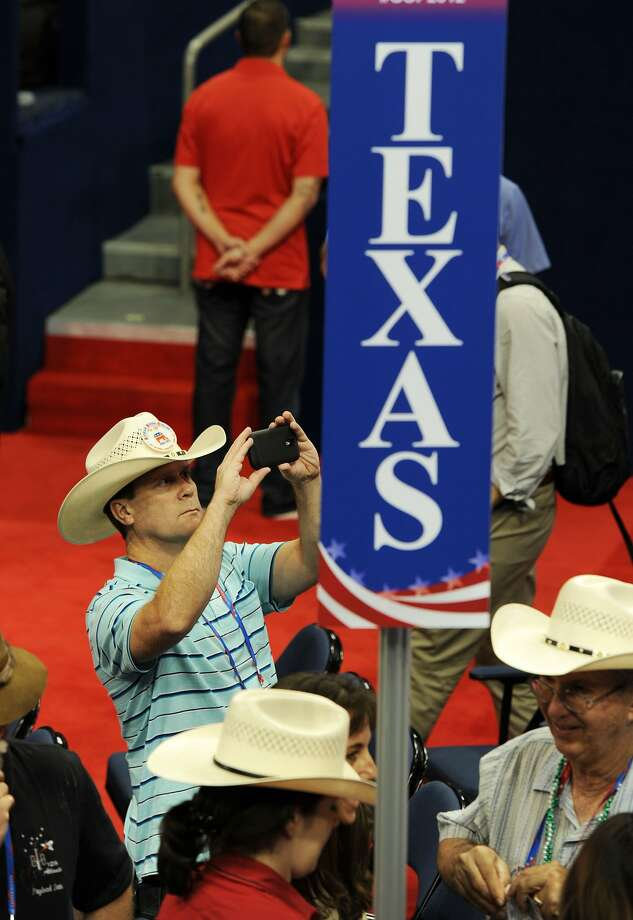 A delegate from Texas trains his camera phone on the US National Debt Clock after the chairman of the Republican National Convention (RNC) Reince Priebus (not in photo) gaveled the convention to order at the Tampa Bay Times Forum in Tampa, Florida, on August 27, 2012. The Republican convention to crown Mitt Romney the presidential nominee opened not with a bang but with a whimper, as the symbolic session was adjourned almost immediately for a day's storm delay.     (ROBYN BECKROBYN BECK/AFP/GettyImages) (ROBYN BECK / AFP/Getty Images)