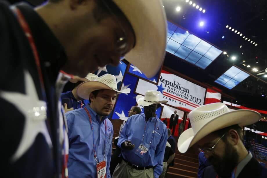 Texas delegates Read King of Denton, left, Jason Kute from Austin, Allen Johnson from Austin and Jeremy Blosser from Ft. Worth gather on the floor of the Republican National Convention in the Tampa Bay Times Forum in Tampa, Fla., on Monday, Aug. 27, 2012. (David Goldman/AP) (David Goldman / Associated Press)