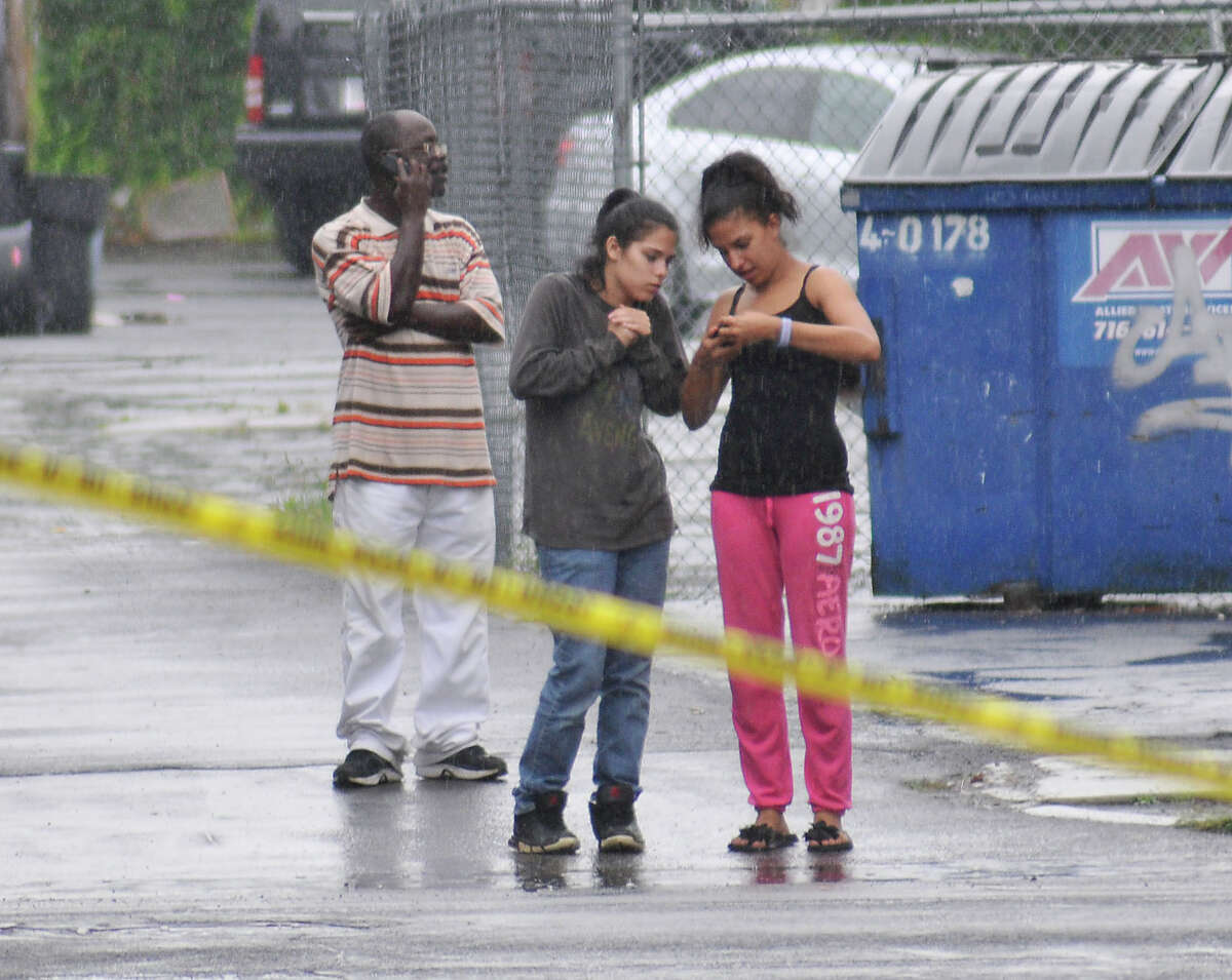Area residents stand behind crime scene tape as Niagara Falls Police crime scene investigators work in the alley where the body of 5-yeat-old Elizabeth Tennant was found, between Third and Forth Streets and Ferry and Walnut avenues on Monday, Aug. 27, 2012 in Niagara Falls N.Y. Authorities said 16-year-old John Freeman and 18-year-old Tyler Best are scheduled to be arraigned Tuesday morning in Niagara Falls City Court in connection with the death of the 5-year-old New York girl. Police have charged Freeman as an adult, and he faces a murder charge. Best is charged with tampering with evidence. (AP Photo/The Niagara Gazette, Dan Cappellazzo) BUFFALO NEWS OUT; BATAVIA DAILY NEWS OUT