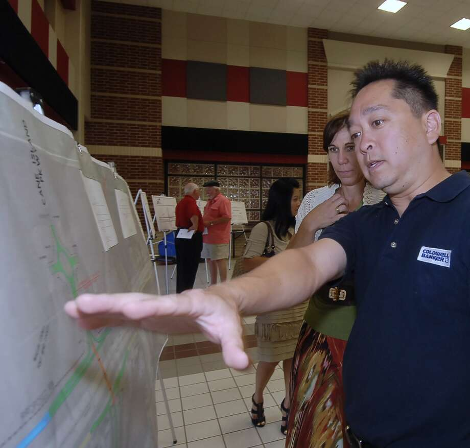 Susan Alford, president of Berg Oliver Associates, an environmental consulting firm; and Lloyd Lee of Coldwell Banker Commercial real estate, look over a schematic of the preliminary engineering design for the proposed Cane Island Parkway and Interstate 10 improvement project during a Texas Department of Transportation public meeting at WoodCreek Junior High School in Katy. Photo:  Tony Bullard 2012 / © Tony Bullard & the Houston Chronicle