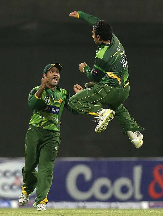 Pakistan's Saeed Ajmal, right, leaps in the air as he celebrates with his teammate Umar Akmal taking the wicket of Australia's Michael Hussey, not pictured, during the first cricket ODI match of a three match series between Australia and Pakistan at Sharjah Cricket Stadium, in Sharjah, United Arab Emirates, Tuesday, Aug. 28, 2012. (AP Photo/Hassan Ammar) Photo: Hassan Ammar, Associated Press