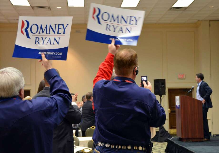 Texans hoist Romney placards and cheer during a delegation meeting at the Republican National Convention. (Jennifer A. Dlouhy / Houston Chronicle)