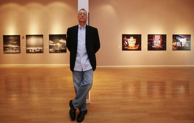"Fotoseptiembre USA director Michael Mehl says the seven separate exhibits in ""Mixed Metaphors"" at Instituto Cultural de México work well together. Susan Burnstine's ""Absence of Being"" (left) and ""Stage"" by Shen Chao-Liang flank him. Photo: Jerry Lara, San Antonio Express-News / © 2012 San Antonio Express-News"