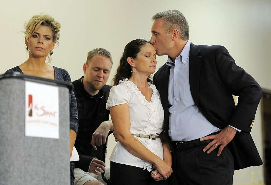 Thomas Teves kisses his wife, Caren, on Tuesday at a news conference called by relatives of victims of the Aurora, Colo., theater shooting. The family members are upset with the way the millions of dollars raised since the tragedy are being distributed and are demanding more of a say. The Teveses lost their son Alex in the July 20 shooting. Photo: Chris Schneider, Associated Press