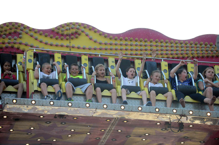 Thrill seekers ride the Ali Baba on the first night of the St. Leo's Fair on Roxbury Road in Stamford, Conn., August 28, 2012. The fair runs Aug. 28 through Sept. 1 with hours on Tues. to Friday, from 6-11 p.m. and Sat. 2-11 p.m. Photo: Keelin Daly / Stamford Advocate