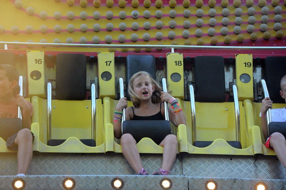 Shannon Hart, 8, rides on the Ali Baba during the first night of the St. Leo's Fair on Roxbury Road in Stamford, Conn., August 28, 2012. The fair runs Aug. 28 through Sept. 1 with hours on Tues. to Friday, from 6-11 p.m. and Sat. 2-11 p.m. Photo: Keelin Daly / Stamford Advocate
