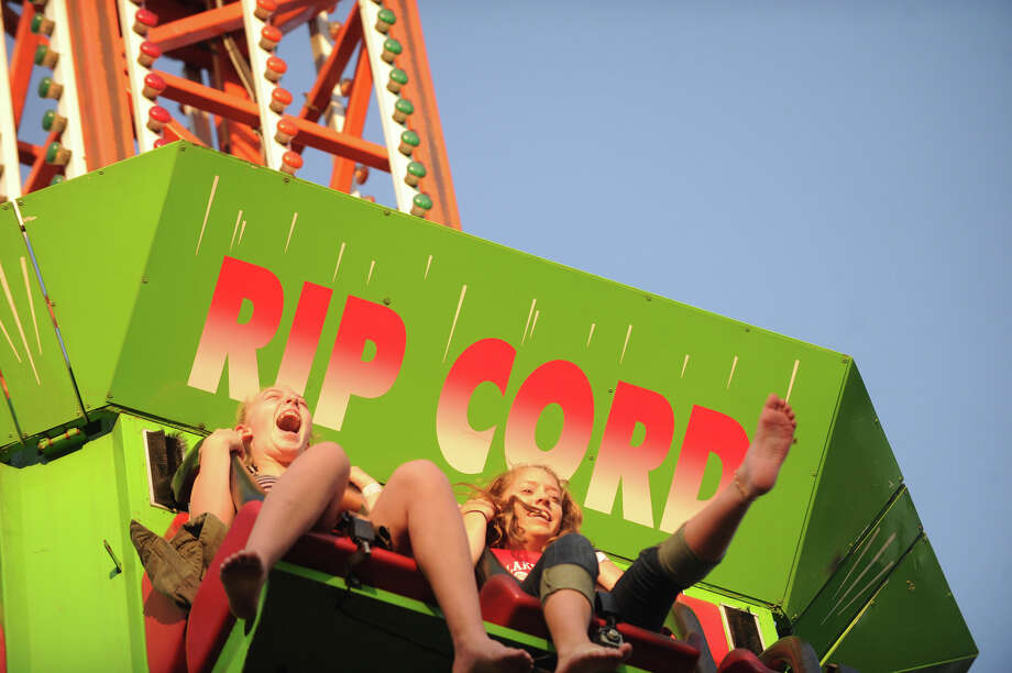 Christina Landle, 13, right, and Skye Griffith, 13, hold on tight as they ride the Rip Cord on the first night of the St. Leo's Fair on Roxbury Road in Stamford, Conn., August 28, 2012. The fair runs Aug. 28 through Sept. 1 with hours on Tues. to Friday, from 6-11 p.m. and Sat. 2-11 p.m. Photo: Keelin Daly / Stamford Advocate