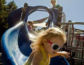 Chloe Griffin (center) descends the playground slide in style as her mother Jolean looks on, at Howarth Park in Santa Rosa, August 28, 2012.