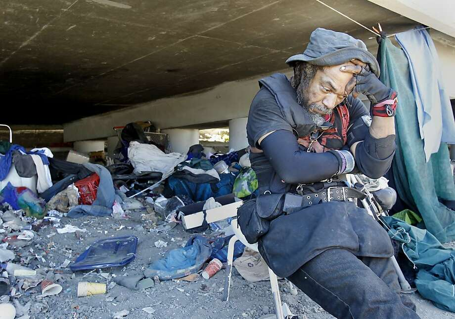 Kane Edwards pauses while collecting his belongings from the encampment at Fifth and King streets where he had lived for months. Photo: Brant Ward, The Chronicle