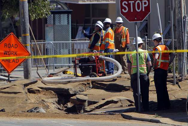 Work crews look over the damage to the road after when a sink hole developed from a water main rupture at the intersection of Sunnydale Avenue and Cora Street in San Francisco, Calif., on Tuesday, August 28, 2012. Photo: Carlos Avila Gonzalez, The Chronicle