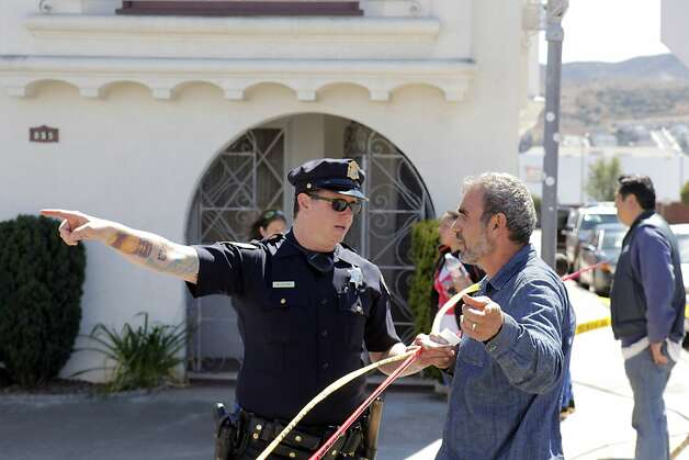 San Francisco Police Officer, Broderick Elton, speaks with Ahmed Shwasheh, a local merchant after a water main ruptured at the intersection of Sunnydale Avenue and Cora Street in San Francisco, Calif., on Tuesday, August 28, 2012. Photo: Carlos Avila Gonzalez, The Chronicle