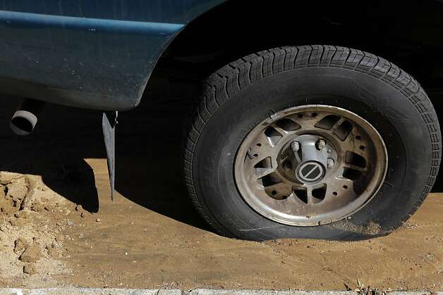 Mud surrounds the tire of a truck on Peabody Street after a water main ruptured at the intersection of Sunnydale Avenue and Cora Street in San Francisco, Calif., on Tuesday, August 28, 2012. Photo: Carlos Avila Gonzalez, The Chronicle