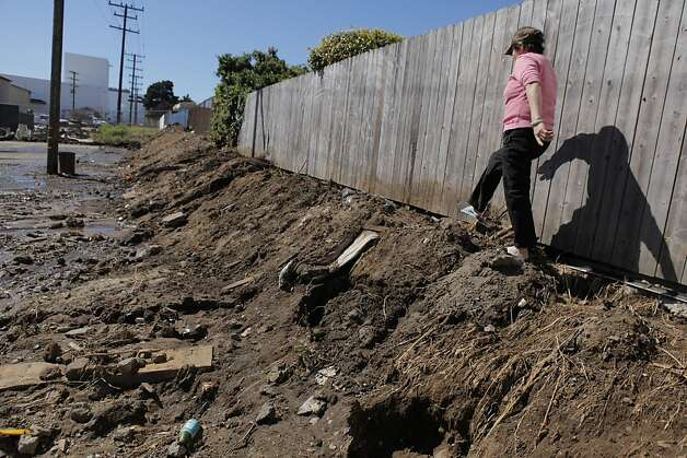 A Visitacion Valley resident walks along a patch of dirt where a retaining wall was washed away after a water main ruptured. Photo: Carlos Avila Gonzalez, The Chronicle