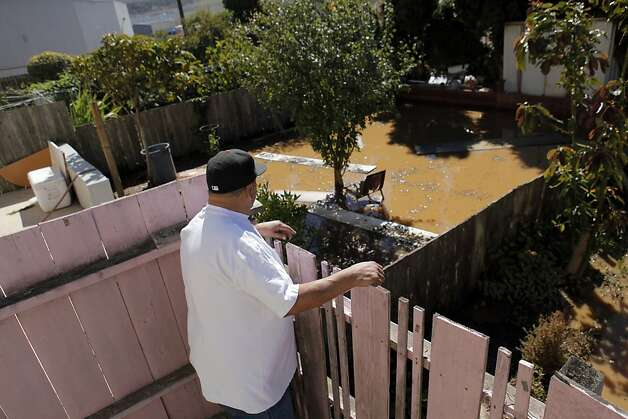 Pete Alvarez looks over the damage to his and his neighbor's back yards after a water main ruptured at the intersection of Sunnydale Avenue and Cora Street in San Francisco, Calif., on Tuesday, August 28, 2012. Photo: Carlos Avila Gonzalez, The Chronicle