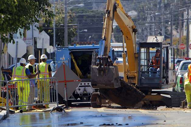 Work crews use an excavator to remove parts of the roadway that were destroyed after a water main ruptured at the intersection of Sunnydale Avenue and Cora Street in San Francisco, Calif., on Tuesday, August 28, 2012. The area remained closed so crews could determine the damage to underground utility lines in the area. Photo: Carlos Avila Gonzalez, The Chronicle