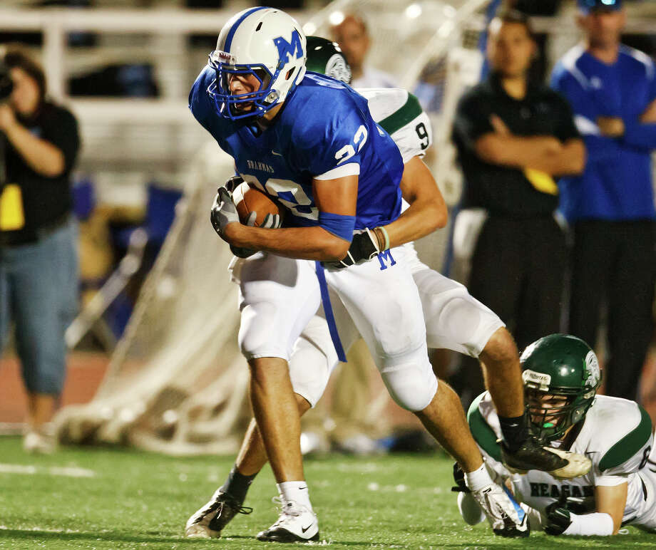 MacArthur tight end Jace Amaro carries Reagan defensive back Shane Ax for extra yardage on a first quarter reception in their game at Comalander Stadium on Oct. 16, 2010. MARVIN PFEIFFER/mpfeiffer@express-news.net Photo: MARVIN PFEIFFER, Express-News / Express News 2010