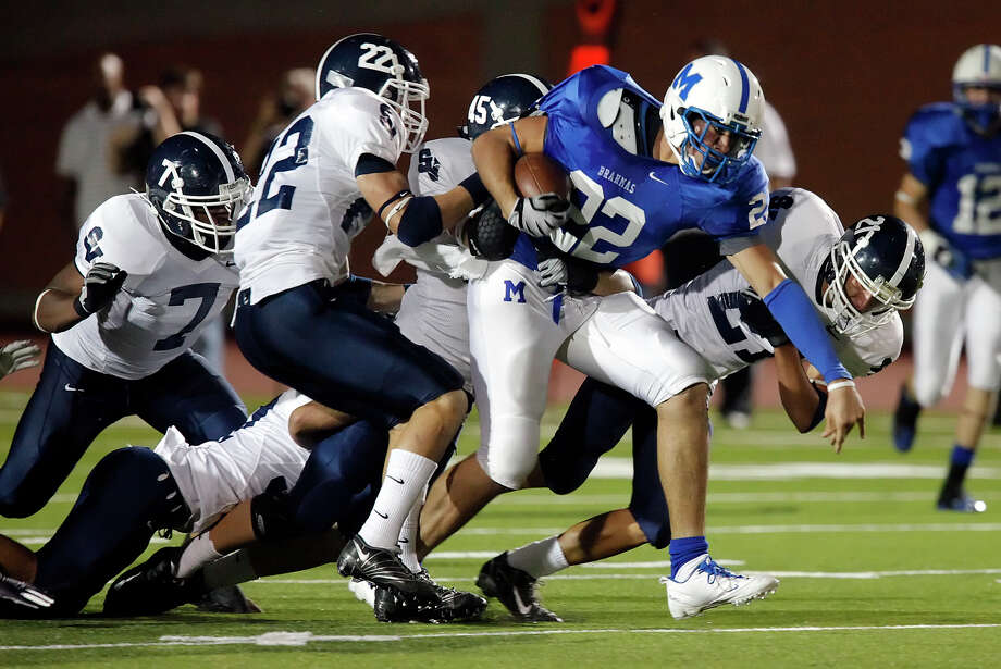MacArthur's Jace Amaro (22) attempts to fend off tackles from a slew of Smithson Valley defenders during their game at Heroes Stadium on Friday, Oct. 2, 2009. Kin Man Hui/kmhui@express-news.net Photo: KIN MAN HUI, Express-News / kmhui@express-news.net