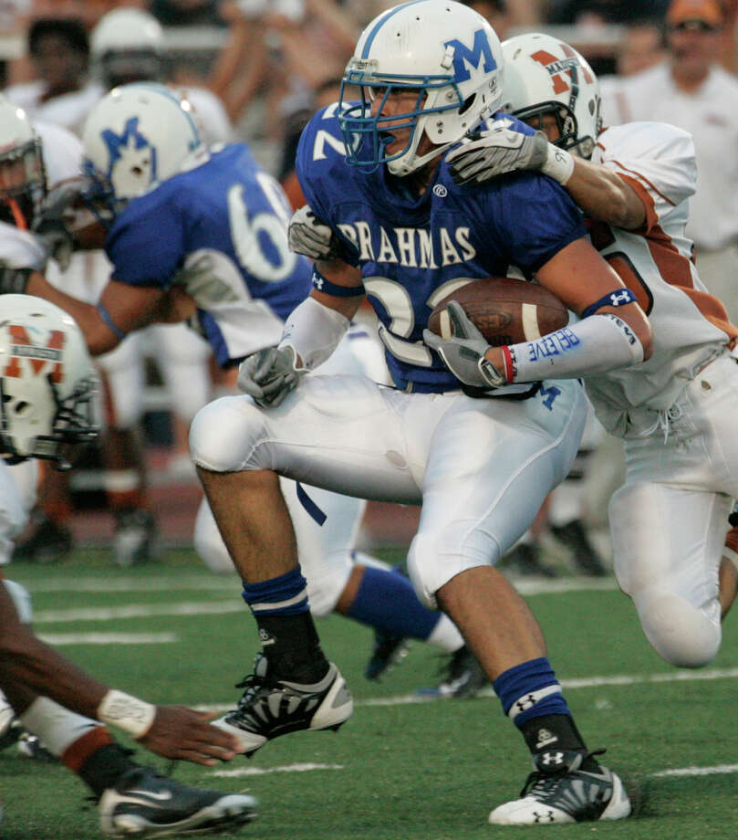 MacArthur tight end Jace Amaro (22) is dragged down from behind by Madison defender Amos Lozano, right, as the MacArthur Brahmas host the Madison Mavericks at Commalander Stadium in San Antonio, Sautrday, Sept. 27, 2008. Madison takes a 34-21 lead into halftime. ( Photo by J. Michael Short / SPECIAL ) Photo: J. MICHAEL SHORT, Express-News / SAN ANTONIO EXPRESS-NEWS