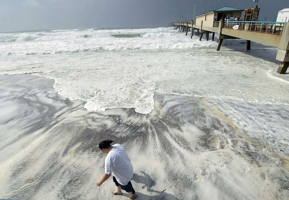 L'Rena Anderson leans into the wind as she walks along the beach on Okaloosa Island in Fort Walton Beach, Fla., Tuesday, Aug. 28, 2012. Anderson was among many local residents who turned out to watch the effects of Hurricane Isaac as it churns through the Gulf of Mexico toward an expected landfall in Louisiana. (AP Photo/Northwest Florida Daily News, Devon Ravine) Photo: Devon Ravine, Associated Press