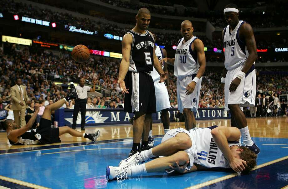 Forward Dirk Nowitzki #41 of the Dallas Mavericks grabs his knee after colliding with Ime Udoka #5 of the San Antonio Spurs on March 23, 2008 at American Airlines Center in Dallas, Texas. (Ronald Martinez / Getty Images)